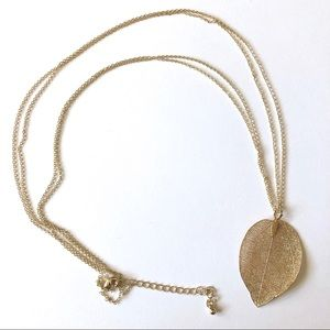 Gold tone double stranded necklace w/leaf pendant